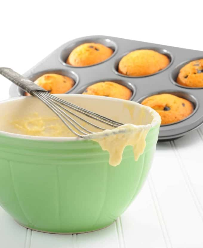 Green Bowl with Muffin Batter, Wire Whisk and Muffin Tin with Fresh Baked Muffins