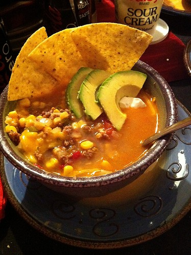 Homemade Taco Soup in a Brown Bowl with Tortilla Chips and Sliced Avocado