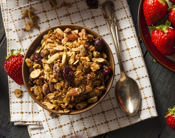 Bowl of maple granola with almonds and dried cranberries on a white placemat with fresh strawberries and a spoon