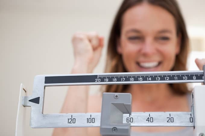 Happy Smiling Woman Standing On Scale Showing Weight Loss