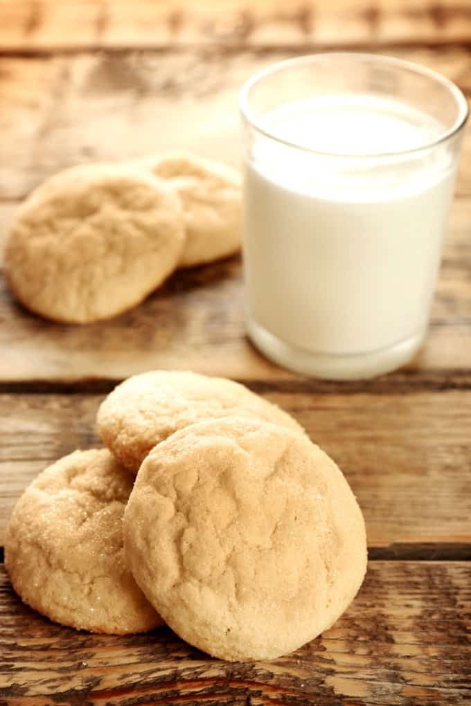 Simple sugar cookies on a wooden table with glass of milk