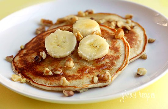 Two banana nut pancakes on a white plate topped with banana slices and chopped walnuts