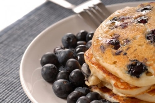 Stack of Blueberry Pancakes on a plate with fresh blueberries
