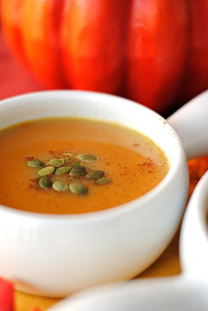 White bowl of gingered pumpkin soup topped with pepitas