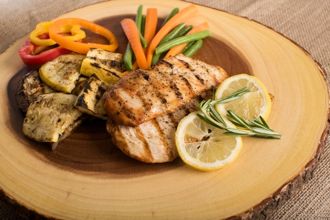Grilled chicken breasts and vegetables on wood platter with lemon slices.