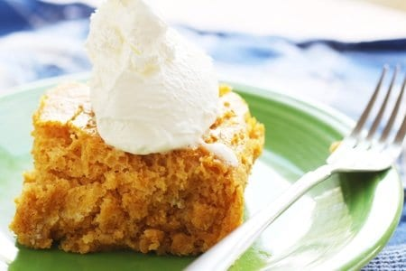 Piece of pumpkin cake with whipped topping on a green plate with a fork