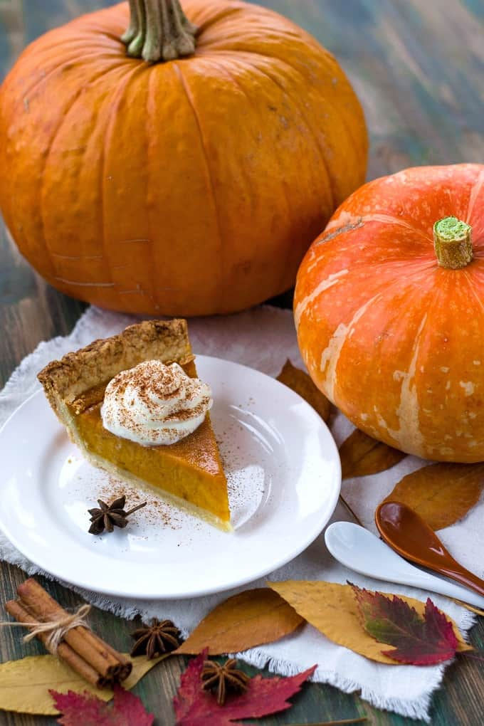 Slice of pumpkin pie topped with whipped cream and two pumpkins in the background