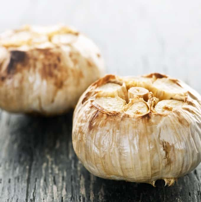 Close up of fresh roasted garlic bulbs on wood table