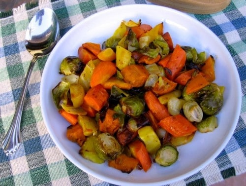 Roasted Brussels Sprouts Carrots Sweet Potatoes and Onions on a white plate with a serving spoon