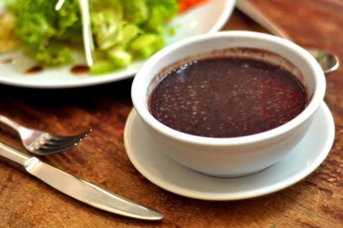 Bowl of black bean soup with a side green salad