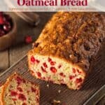 Loaf of cranberry orange oatmeal bread on wood cutting board with two slices cut and laying in front.