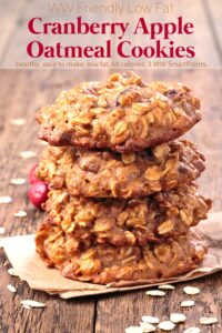 Four cranberry apple oatmeal cookies stacked on top of each other on wooden table with oats and cranberries scattered about.