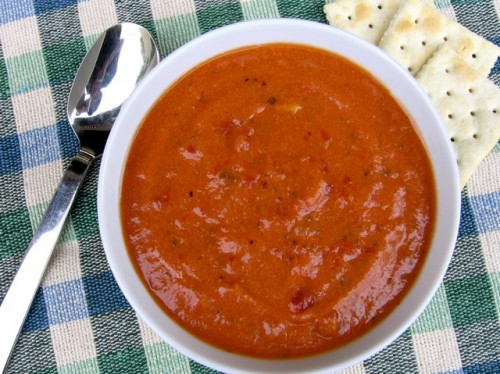 Bowl of Chunky Tomato Soup with a spoon and saltine crackers on a checkered table cloth