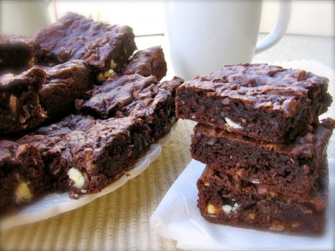 Stack of Three Chocolate Coconut Cake Mix Bar Cookies Next to a Plate Filled with Chocolate Cookie Bars
