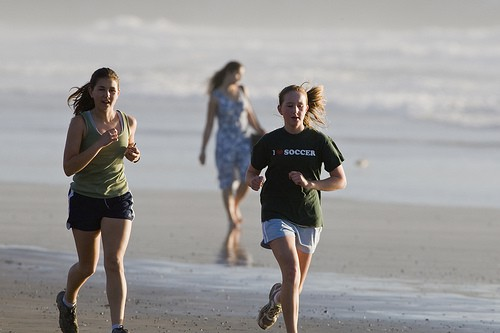 Two young women jogging on the beach