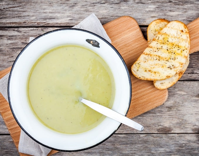 Artichoke soup in a white bowl with a spoon on a wood cutting board with toasted ciabatta