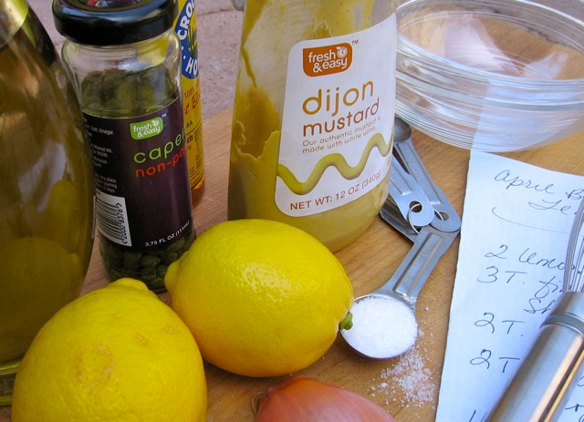 Two lemons, Dijon mustard, capers, salt and recipe for making salad dressing.