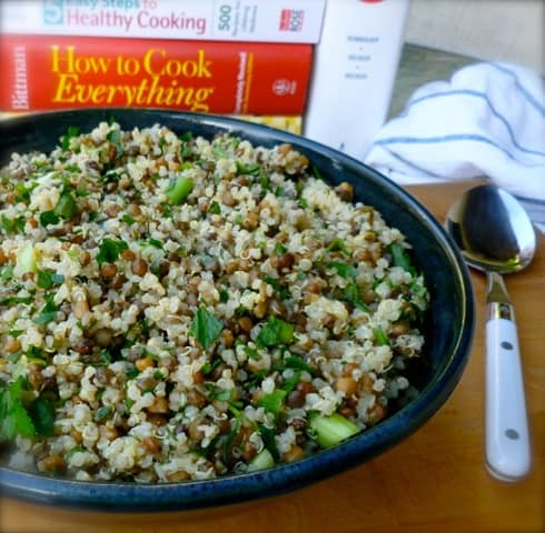 Lemon lentil quinoa salad in blue bowl with cookbooks behind and spoon alongside