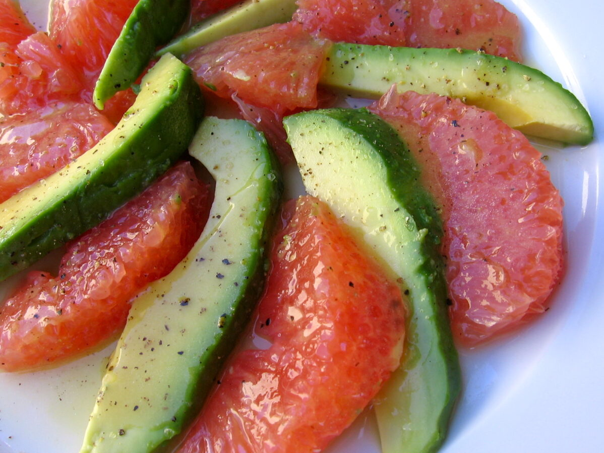 alternating avocado and pink grapefruit wedges spiraled on white plate