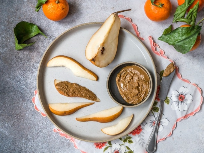 Fresh sliced pear with peanut butter on plate with tangerines scattered about
