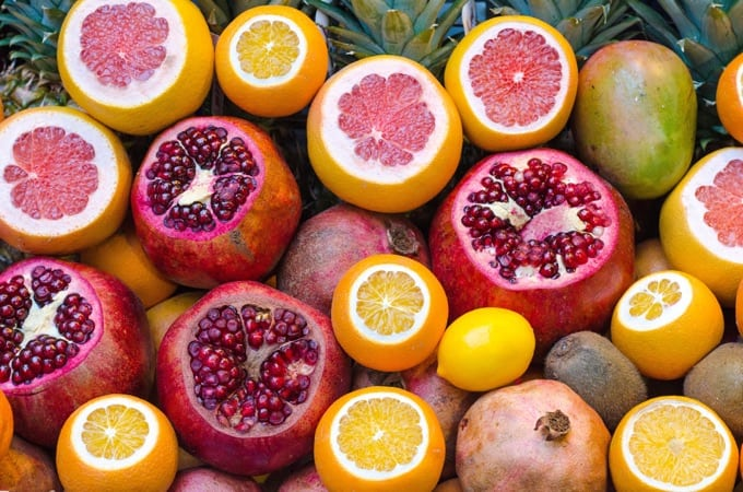 Fresh pomegranate, pink grapefruit and oranges with the top sliced off sitting among other fruit