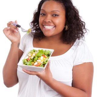 Young woman eating fresh green salad