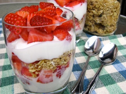 Strawberry, yogurt and granola parfaits in clear glasses on checked tablecloth