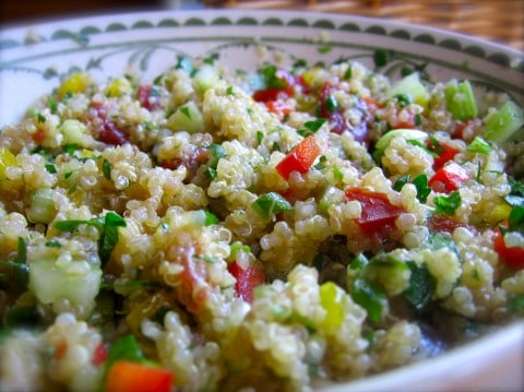 Quinoa salad with chopped red, green and yellow peppers in decorative bowl close up