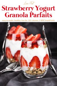 Two Strawberry Granola Parfaits with non-fat Greek yogurt and honey or maple syrup in glasses with spoons.