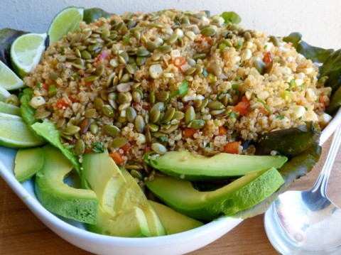Lightened Up Quinoa & Corn Salad with toasted Pumpkin Seeds and avocado slices on serving plate with spoon.