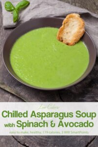 Chilled asparagus soup with crusty bread in dark bowl on wood table.