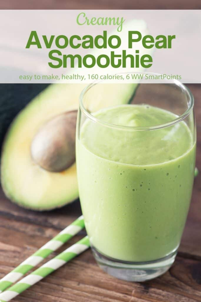 Creamy avocado pear smoothie in tall glass on wood table with two straws and avocado cut in half