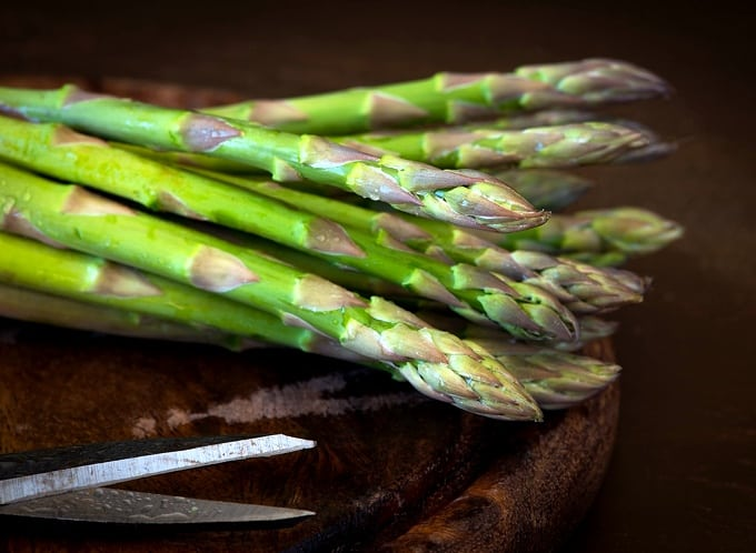 Fresh asparagus spears on dark wood cutting board.