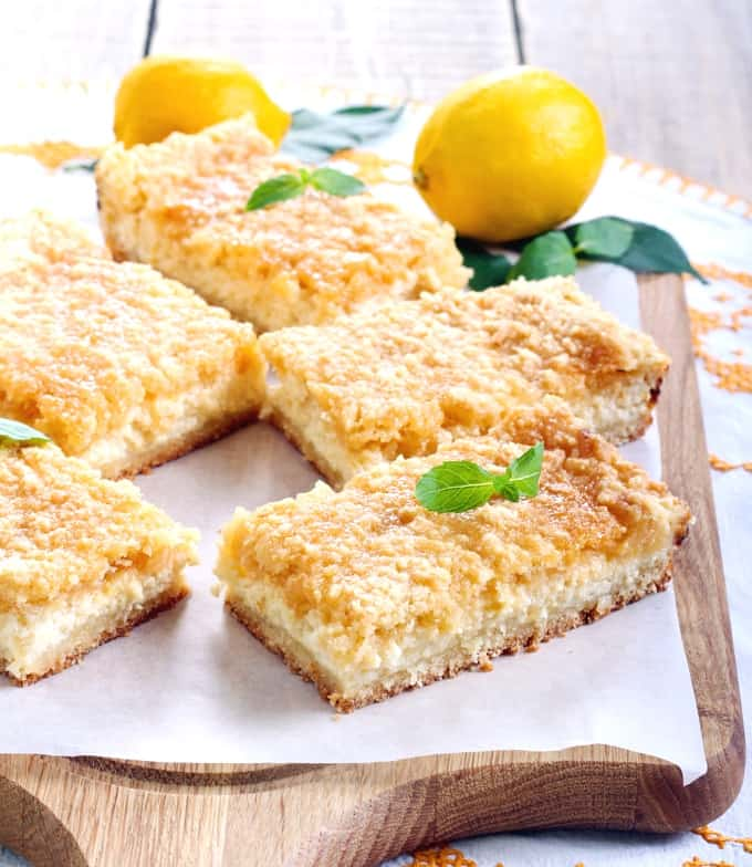 Lemon cream cheesecake cookie bars on parchment paper on wood cutting board with two lemons.