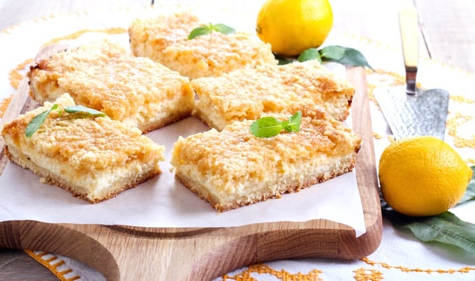 Lemon cheesecake bars on parchment lined wood cutting board with two whole lemons.