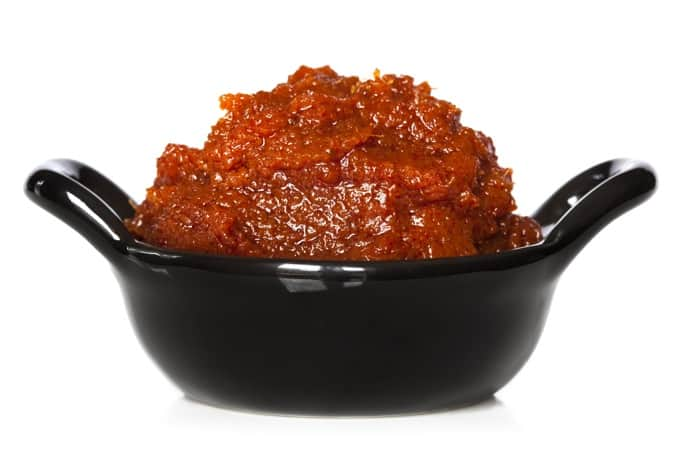 Thai red curry paste in small black bowl, isolated on white