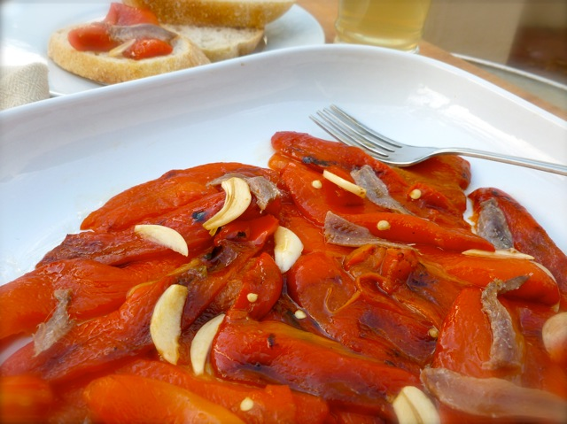 Roasted Red Peppers with Anchovies with a fork on white plate.