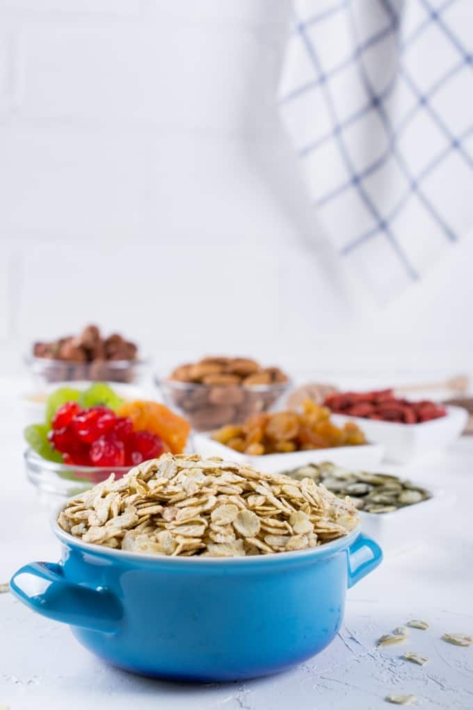Blue bowl with rolled oats and various bowls with healthy granola bar ingredients such as dried fruit, pumpkin seeds and nuts