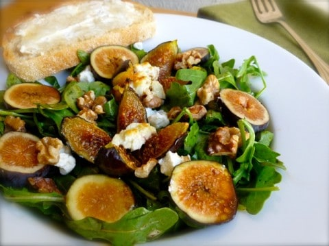 Warm Fig and Goat Cheese Salad on a white plate with toasted bread and butter