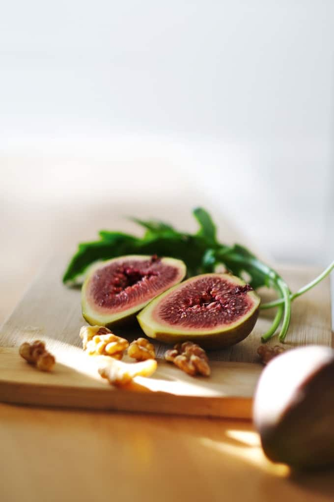 Fresh fig cut in half on wood cutting board with walnuts and arugula