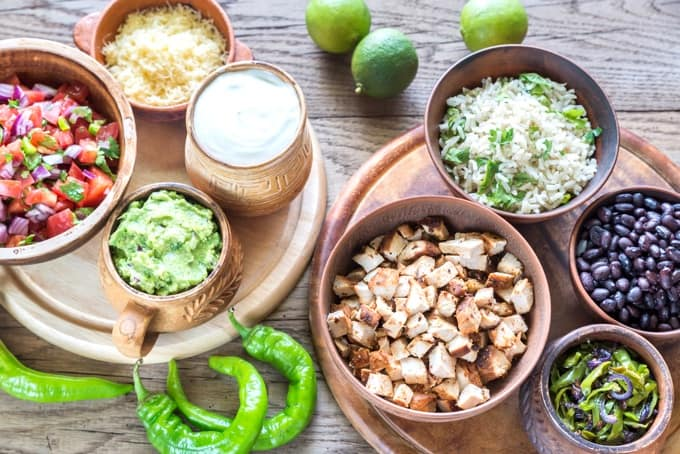 Taco salad ingredients in individual bowls: pico de gallo, shredded cheese, guacamole, cooked chicken, seasoning brown rice, black beans and jalapeños