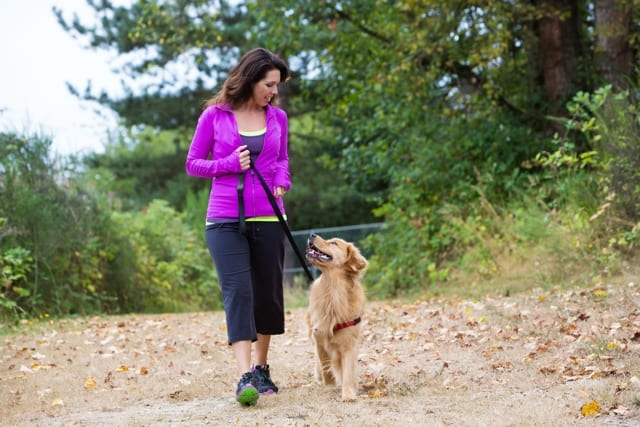 Women in workout clothes walking her dog on a leash
