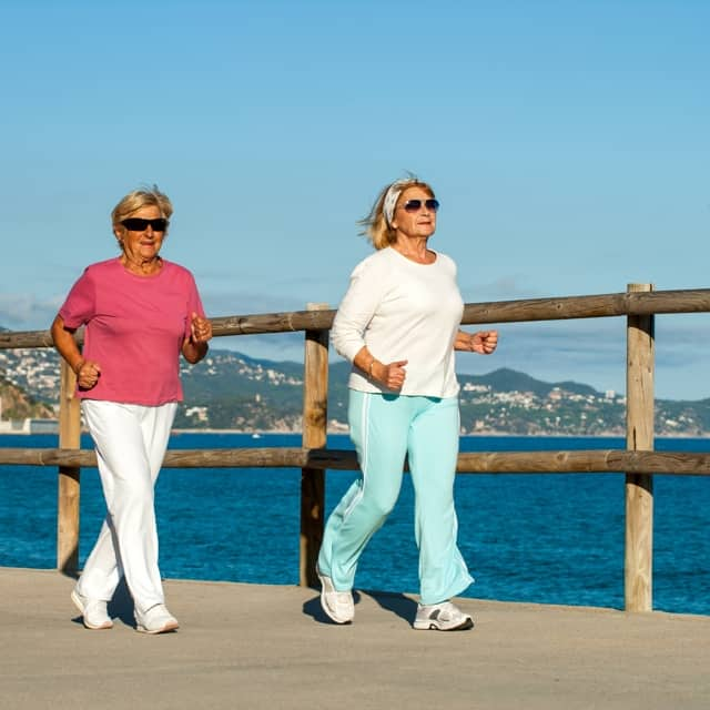Two women walking along dock with water in background