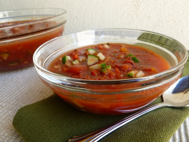 Chunky Gazpacho in small glass bowl with a spoon and green napkin.