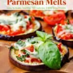 Sliced baked eggplant parmesan melts topped with fresh basil on wood table.