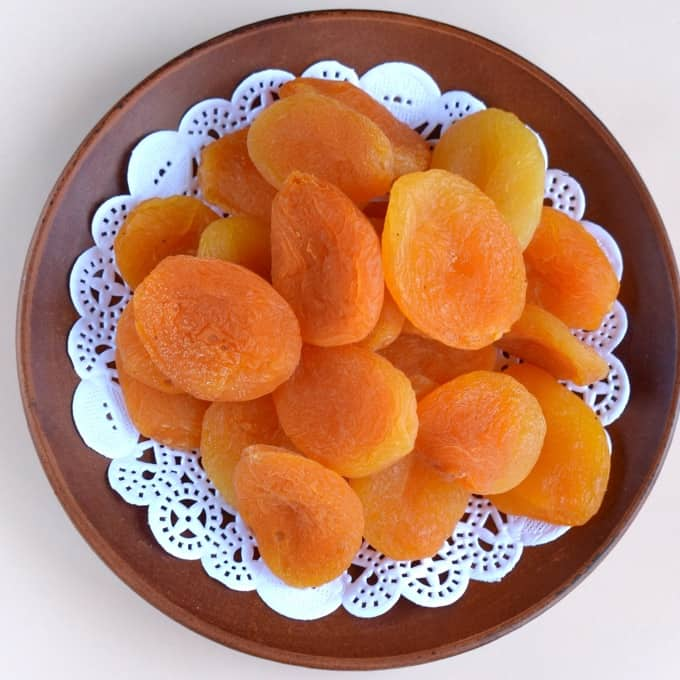 Dried apricots on a brown plate from above