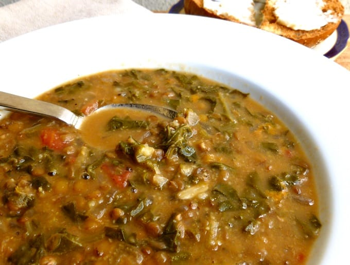 Bowl of Lentil Soup with Swiss Chard in a white bowl with spoon