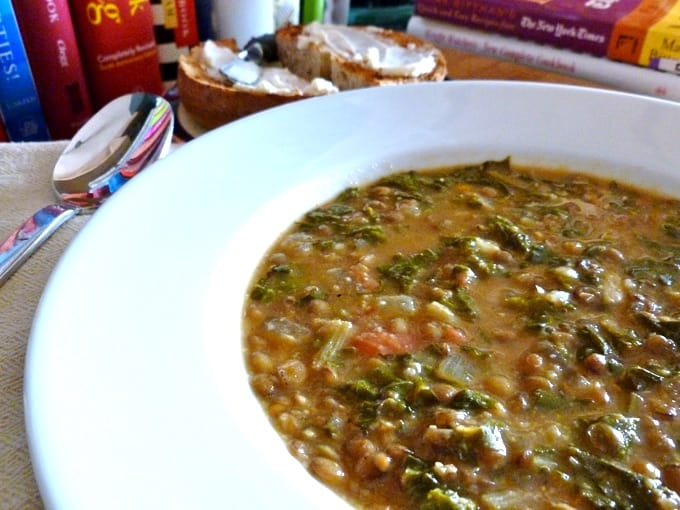 Lentil Swiss Chard soup in a white bowl with spoon and cookbooks in the background