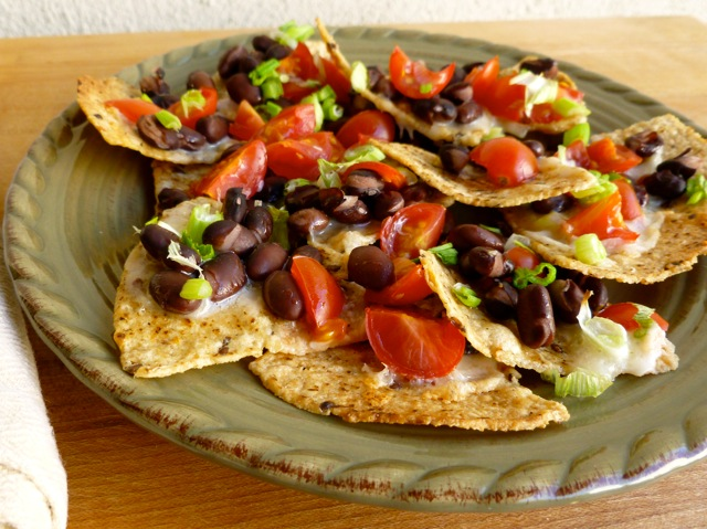 Cheese and Black Bean Nachos on green pottery plate.