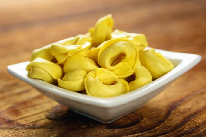 Tortellini in a white dish on wood table